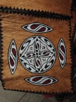 """""""KHOMBOW"""" BARK PAINTINGS """"Khombow"""" bark paintings are the work of Sentani people that have existed since their ancestors who were used as clothing (Malo) by married Sentani women. Khombow has a very high philosophical value for the Sentani people, because in the past khombow as clothing was only used 3 times in their lives namely; at the time when a child is born it is used as a wrapper for the baby, when a woman is married and when someone dies, khombow is used to wrap the body.  The motifs painted on Khombow bark have sacred meanings and meanings for Sentani people, because there are motifs that are only exclusively owned by an Ondofolo (traditional leader), Khoselo and other customary tools such as the Crocodile and Yoniki motifs. From the results of the field study and the documentation of the motifs painted in Khombow, there have been approximately 12 motifs such as the sun motif, Snake motif, Lizard motif, Lizard, Fish, Stork Feet, Eel, Bat, Flying Squirrel, Leaves, Forest and Spiral or circular flowers. While from its function there are paintings related to aspects of religion and mythology such as Hu and Yoniki's paintings, as well as paintings related to socio-economic aspects, such as Fouw, Kasindale, Isomo and Kino.  The technique of making Khombow bark has not changed traditionally but has not used a machine, only the equipment that has been changed has used modern equipment such as cutting trees using iron axes, machetes to peel Khombow bark and iron plates to pound the skin to be long and wide dried and later as the main material for painting. At present the Khombow bark painting is still preserved by Sentani people, especially those in the Asei village, East Sentani District, Jayapura Regency, even though its function has changed, it is no longer as clothing but has been made as one of the Papuan souvenirs fromSentani."""